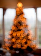 Deliberated blurred Christmas tree decorated with silver and white ribbons to get the out of focus images of the lights in family home
