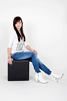 Young woman wearing a white top and jeans posing on a black cube seat