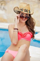 Attractive young woman in red bikini with cowboy hat and sun glasses sitting at swimming pool