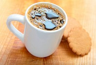 a cup of black coffee with ginger cookies