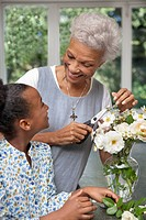 Older woman and granddaughter arranging flowers