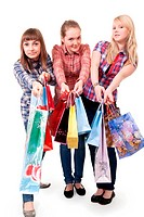 Three girls with colorful shopping bags on white background