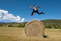 Basalt, Colorado, USA.A man in a suit appear to be jumping over a hay bale in a field.