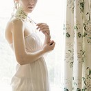 Slender young woman wearing a white dress with pale skin holding babys breath flowers, against a window with rain drops on it surrounded by floral cur...