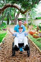 Caring nursing home orderly pops a wheelie with an elderly man´s wheelchair. They are having fun.