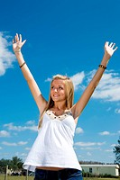 Blond teen girl outdoors raising her arms in praise.