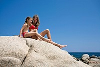 Mother, 40, and daughter, 7, sunbathing on the rocky coast of the bay of Algajola, north-west coast, Balagne region, Corsica, France, Europe