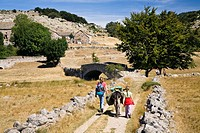 Mother and daughter walking with a donkey during a family-hike with a donkey in the Cevennes Mountains, France, Europe