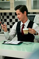 Businessman text messaging on the phone while having coffee in the office pantry