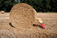 Little girl pushing a big straw bale, Saxony, Germany, Europe