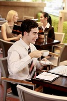 Businessman drinking coffee while looking at laptop, businesswomen sitting in the background
