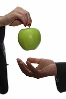Businesswoman offering apple to businessman..