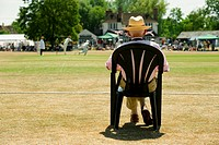 senior man watching a game of cricket on a picturesque English village green