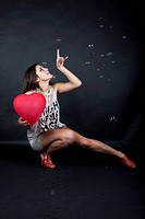 Young woman with a heart balloon, white top, high heels and soap bubbles