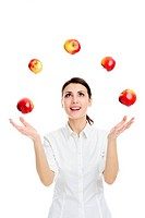 An image of happy young woman playing with red apples