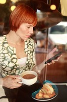 Bakery.Woman checking her smart phone while sipping cafe au lait in neighborhood coffee shop and bakery