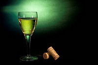White wine in a glass, on black_green background. Art background