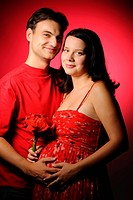 Happy pregnant couple over red background