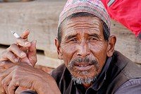 Man with a hat holding a cigarette, portrait, Bhaktapur, Kathmandu Valley, Nepal, Asia