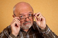 Elderly man, 59, putting on glasses, questioning look