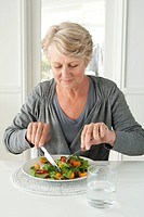 Mature Woman Eating Salad.