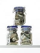 Three jars of money.Three closed jars filled with paper US money