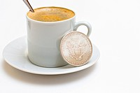 Cup of coffee with a silver dollar coin.