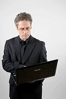 Businessman wearing a black suit holding a laptop