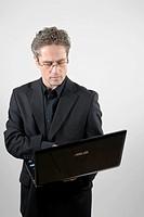 Businessman wearing a black suit holding a laptop