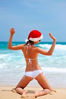 Woman on the beach in santa´s hat
