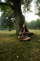 Young woman holding her hands against her chest and meditating in nature. Taken in Lipica, Slovenia. Concept: teenagers and nature, spiritual teenager...