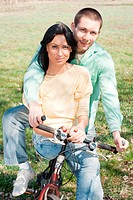 Loving couple on bike outdoors.