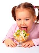 Cute little girl licks fruit salad, isolated over white