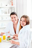 Young happy couple at breakfast in the kitchen
