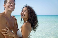 Couple together at the beach, looking up and smiling