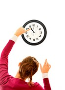 A picture of young woman changing time on a big clock