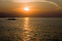 Indonesia. Bali. A sunset over ocean and a boat silhouette.