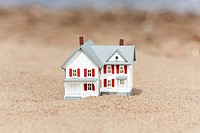 Artificial model of the cottage on the sand, selective focus