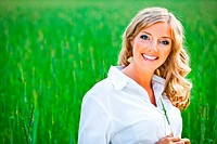 Blond woman portrait outdoor on green field