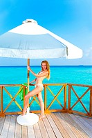 Young woman tans on a terrace of water villa on ocean Maldives