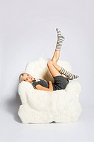 portrait of beautiful blonde sitting on big white furry arm_chair and putting on long striped socks