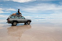 a man sitting on top of jeep in salt desert