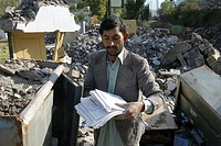 A hospital administrator checks the papers from a cuboard of the destroyed hospital in Hatian, Kashmir, Pakistan