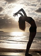 Silhouette Woman Doing Yoga Pose On Beach