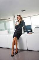 Young business woman drinking at home/hotel