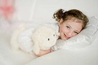 Girl lying on a sofa with a stuffed animal