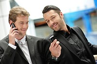 Two young businessmen with mobile phones