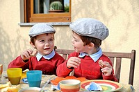Twin boys, 4, wearing flat caps, sitting and eating at a table
