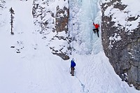 Young man ice_climbing while other man belays him in Banff National Park near Banff, Alberta, Canada.