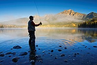 Middle age male fly fishing in Pyramid Lake, Jasper National Park, Alberta, Canada.